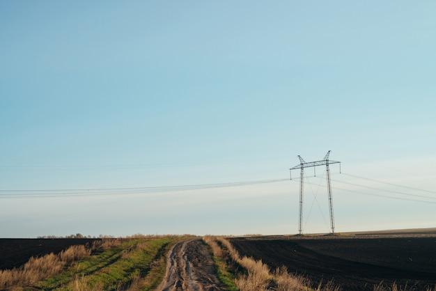 フィールドの電力線のシルエットと自然の風景