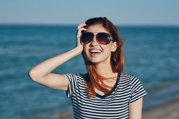 サングラスでビーチの海の近くの自然風景の女性