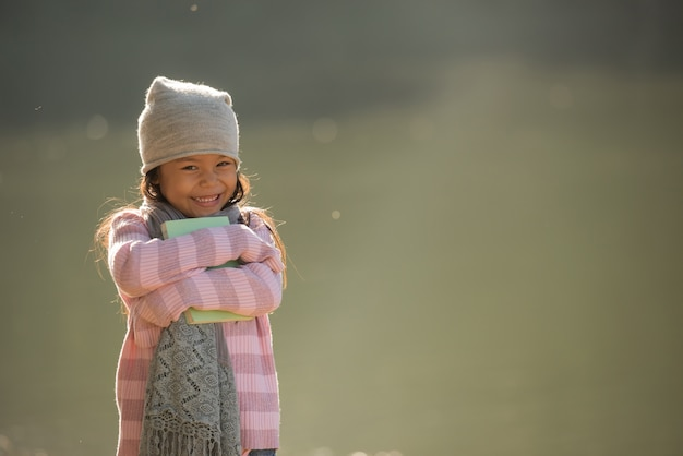 Nature little girl, has happy fun with cheerful smiling face. and have a book in hand.
