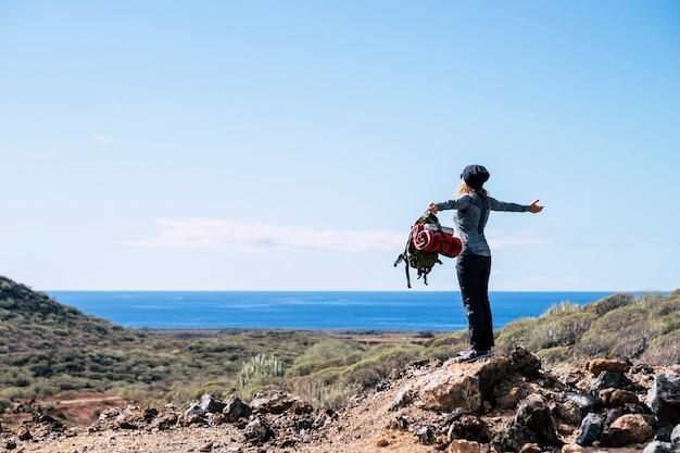 Образ жизни любителя природы с стоящей женщиной, наслаждающейся видом на океан. с вершины холма в пустынной местности - занятия спортом на свежем воздухе для здоровых и свободных людей - альтернативный отпуск