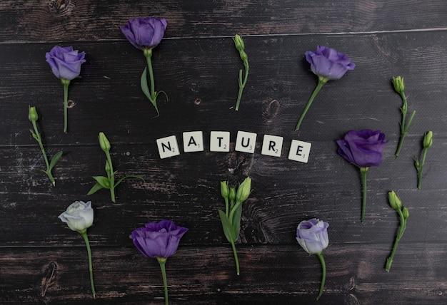 木の表面に紫のトルコギキョウの花に囲まれたスクラブルブロックで作られた「ネイチャー」