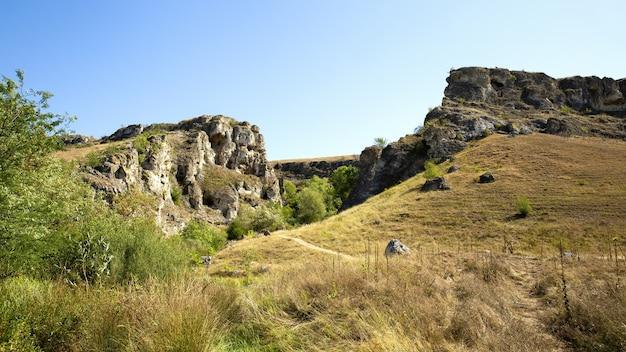 モルドバの自然、岩だらけの斜面、緑豊かな木々、底にハイキングコースがある峡谷