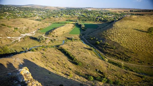 モルドバの自然、流れる川のある谷、まばらな植生のある斜面