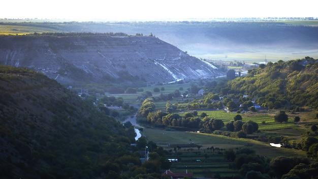 モルドバの自然、流れる川のある谷、それに沿った緑豊かな木々、野原と珍しい建物、岩だらけの丘