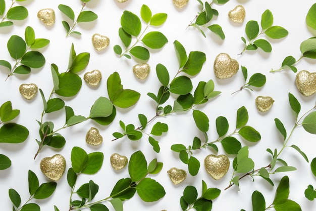 Nature pattern made with green plant branches and golden sparkling hearts on white surface