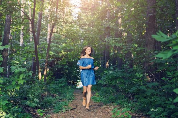 自然、人々、ライフスタイルの概念-夏の森を走るドレスを着た美しい若い女性