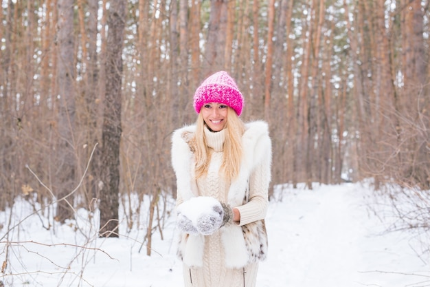 Nature and people concept - attractive blond woman dressed in coat and pink hat in winter park holding snow in her hands.