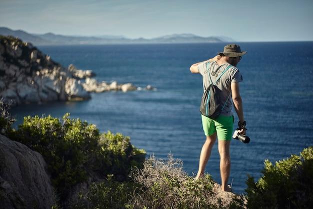 Фотограф-натуралист во время экскурсии к краю обрыва на южном побережье сардинии.