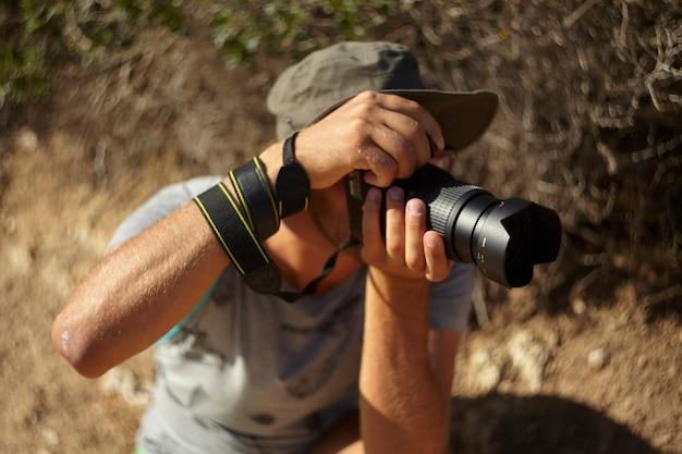Фотограф-натуралист в действии со своим рефлексом во время съемки репортажа