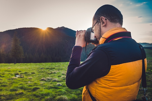 山で写真を撮るカメラを持つ自然写真家の観光客。夢のような夕日の風景、春の緑の牧草地、bsckgroundの山頂。背面図
