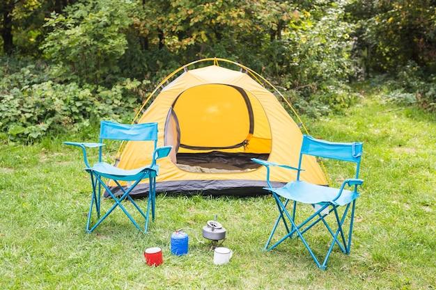 自然、観光、冒険のコンセプト-居心地の良い雰囲気の森のオレンジ色のテント