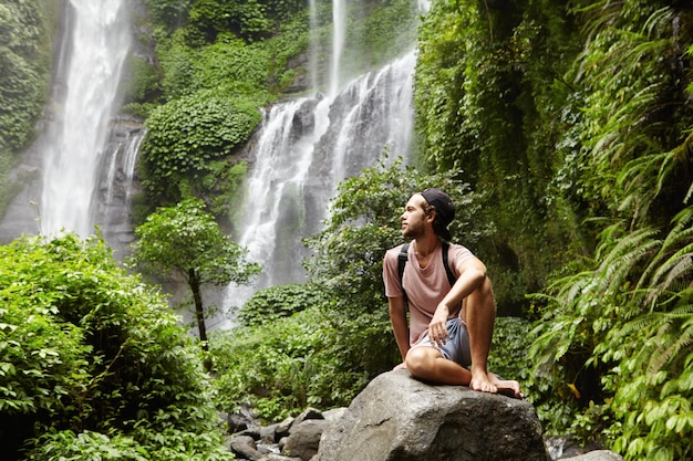 Nature, tourism and people. young barefooted tourist wearing jeans short and backpack sitting on big rock deep inside green rainforest