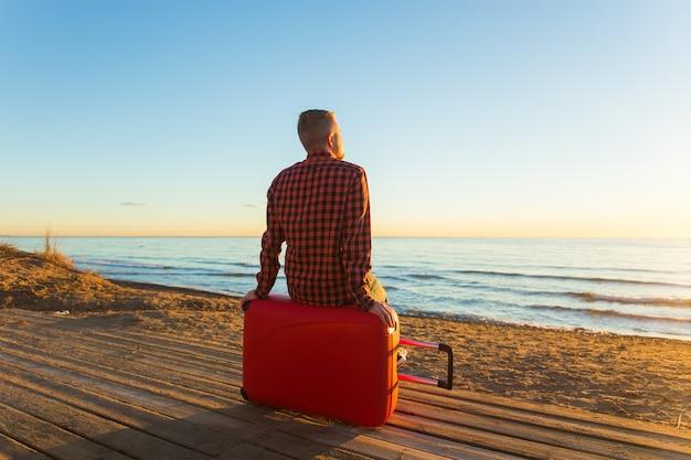 自然、旅行、人々のコンセプト。海の近くの赤いスーツケースに座って夕日を見ている男の背面図