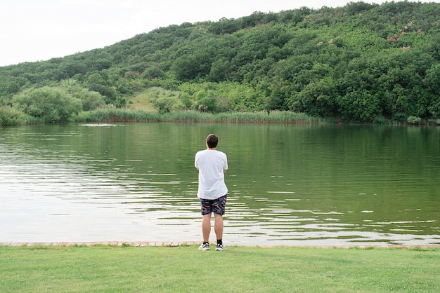 Nature and travel concept. back view of a man standing near the lake