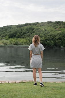Nature and travel concept. back view of a woman standing near the lake