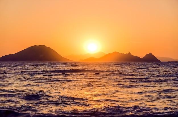 地中海の海岸の海で自然の夕暮れとヴィンテージのビーチホリデーコンセプト夏の夕日...