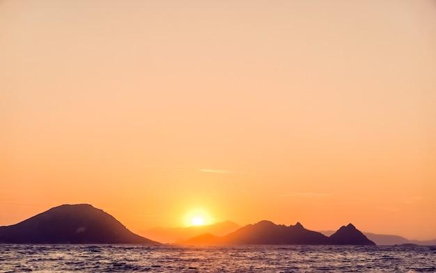 지중해 연안 바다와 산의 전망에서 자연 황혼과 빈티지 해변 휴가 컨셉의 일몰