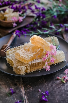 Nature wooden honey dipper and honeycombs on background of wooden