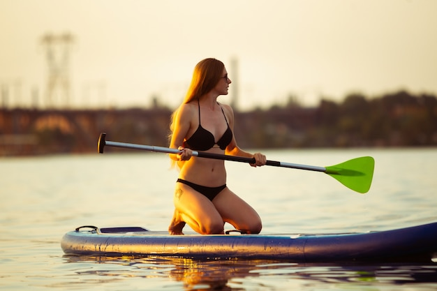 Nature. young woman sitting on paddle board, sup. active life, sport, leisure activity concept