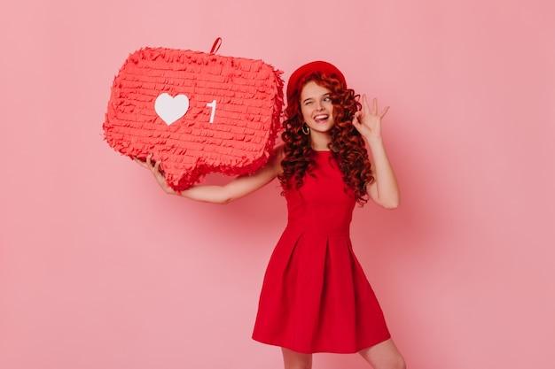 いたずらな美しい巻き毛の女性は、舌、okサイン、ウィンクを示し、ピンクのスペースのように巨大な保持します。
