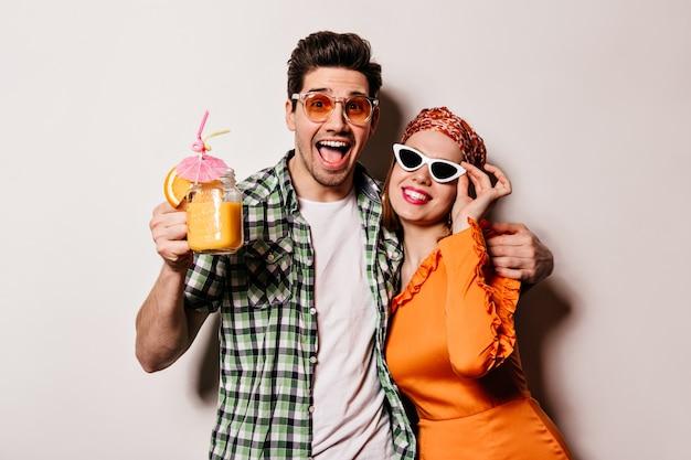 Ragazzo cattivo e ragazza in abiti eleganti e occhiali da sole che abbracciano, sorridono e posano con cocktail arancione su uno spazio bianco.