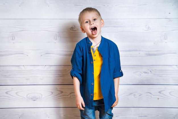 장난 꾸러기 소년은 얼굴을 찡 그리기하고 그의 혀를 튀어 나와