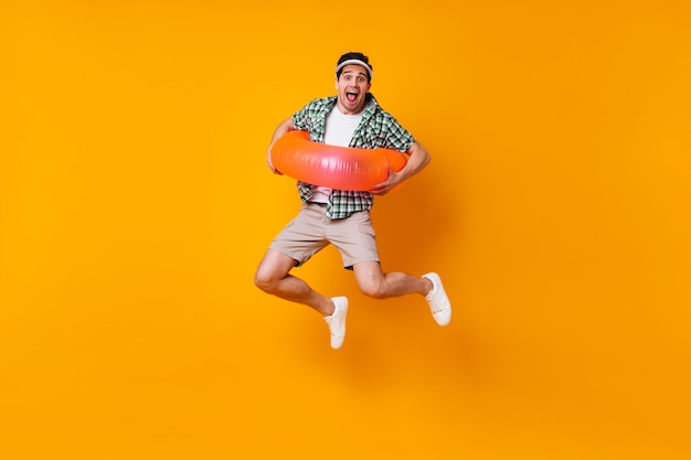 Naughty brunet male dressed in plaid shirt and beige shorts jumping with inflatable circle on isolated space.