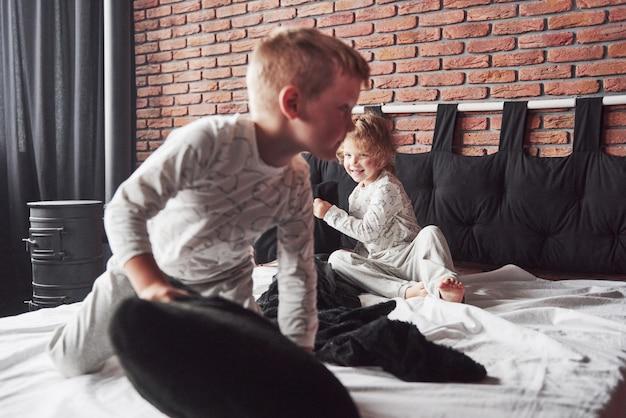 Непослушные дети маленький мальчик и девочка устроили драку подушками на кровати в спальне. им нравится такая игра