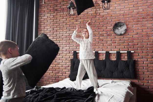 Naughty children little boy and girl staged a pillow fight on the bed in the bedroom. they like that kind of game