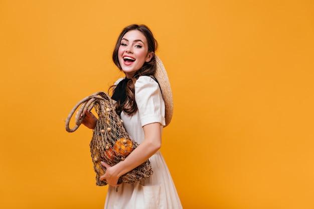 Непослушная темноволосая девушка в белом платье смеется и держит эко-сумку с продуктами на оранжевом фоне.