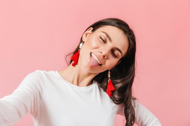 Непослушная девушка в вязаной футболке с длинными рукавами развлекается и показывает язык, делая селфи на розовом фоне.