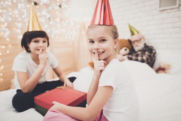 Naughty kids open birthday gift hush gesture.