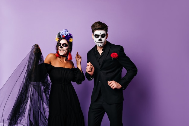 Naughty lady in black and her serious boyfriend are dancing on purple background. portrait of couple in mexican style halloween outfits.