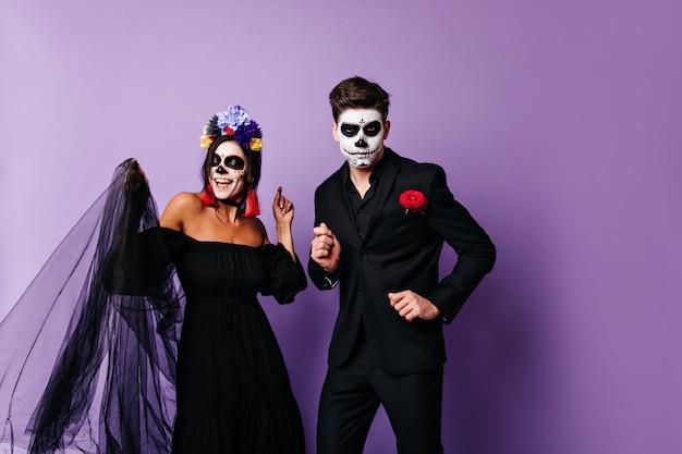 검은 색의 장난 꾸러기 아가씨와 그녀의 진지한 남자 친구가 보라색 배경에 춤을 추고 있습니다. 멕시코 스타일 할로윈 의상에서 한 쌍의 초상화입니다.