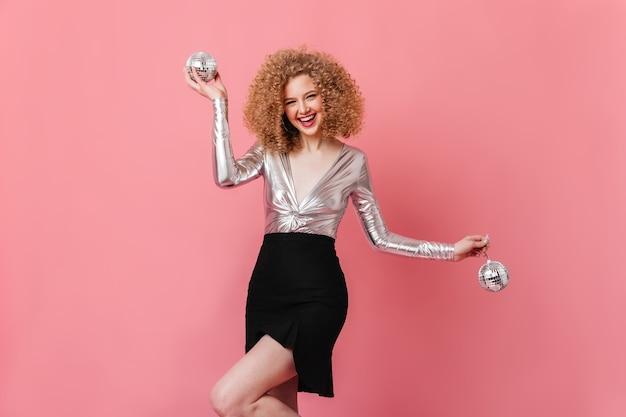 멋진 분위기의 장난 꾸러기 아가씨, 분홍색 공간에 포즈를 취하고 디스코 공을 들고. 은색 옷에 금발 여자의 스냅 샷입니다.