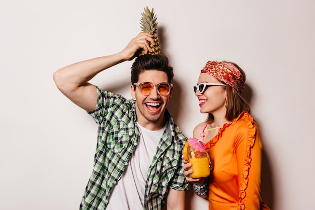 Naughty man in green shirt holds pineapple on his head and looks into camera with smile. lady in orange blouse and glasses holding cocktail.