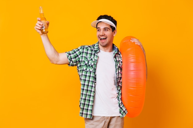 Naughty man picks up bottle of beer, laughs and holds inflatable circle on isolated space.
