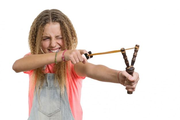 Naughty pretty cheerful teen girl with slingshot