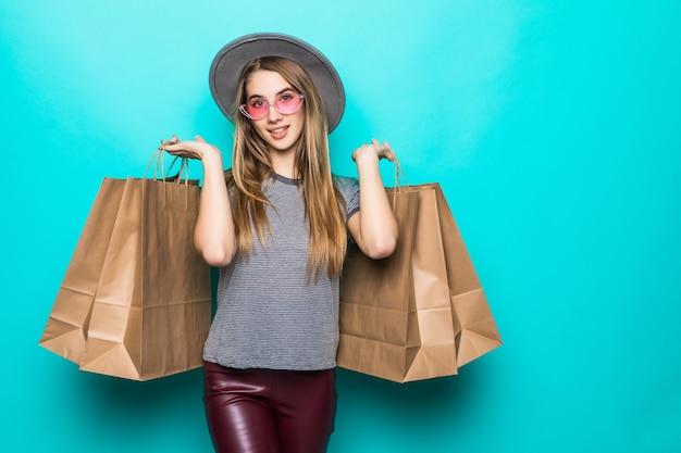 Непослушная женщина покупок улыбается и носит шляпу, изолированные на зеленом фоне