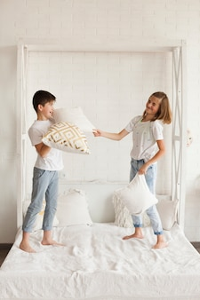 Naughty sibling having pillow fight on bed