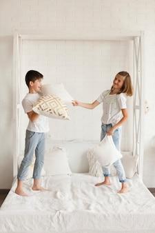 ベッドの上で戦う枕を持ついたずらな兄弟