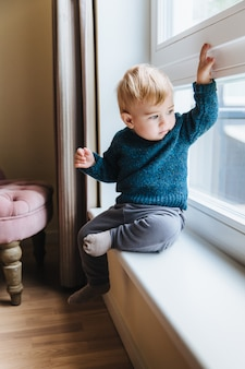 Naughty small kid with blonde hair and blue eyes, sits on window sill, looks out of window