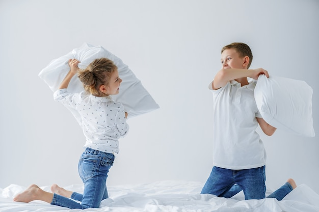 Naughty twins girl and boy friendly fighting staged a pillow fight on the bed in the bedroom.