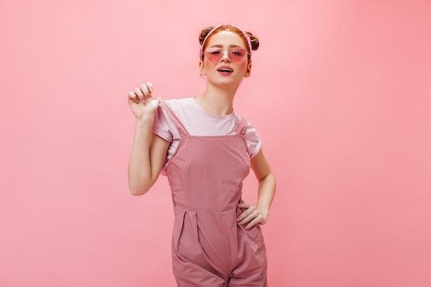 眼鏡とオーバーオールのいたずらな女性はピンクの背景にカメラをのぞきます。