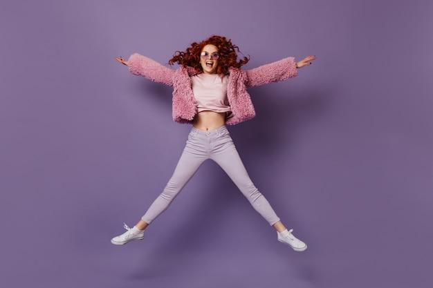 Озорная женщина в сиреневых очках, белых штанах, футболке и розовом эко-пальто прыгает на сиреневом пространстве.
