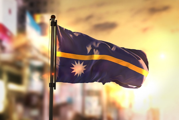 Nauru flag against city blurred background at sunrise backlight
