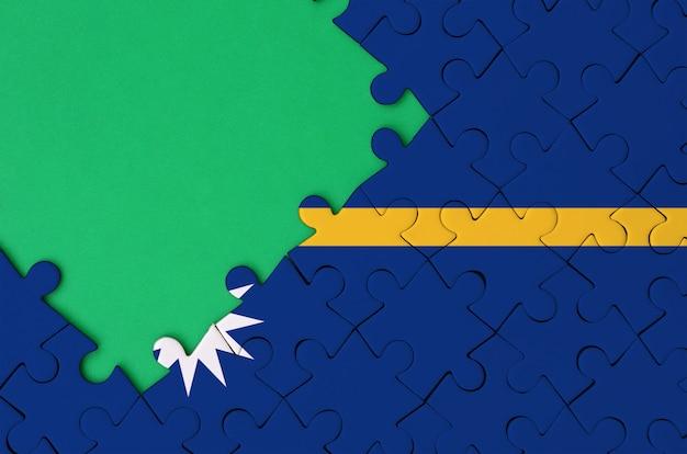 나우루 깃발은 왼쪽에 무료 녹색 복사 공간이있는 완성 된 직소 퍼즐에 그려져 있습니다.