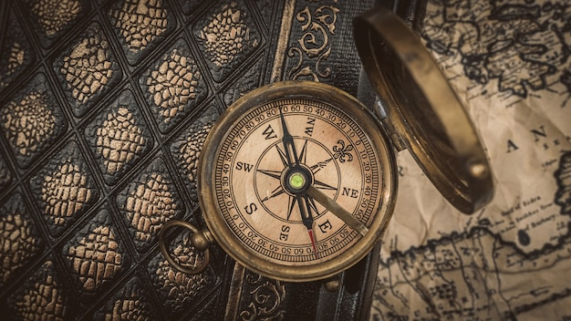 Морской латунный компас на книге