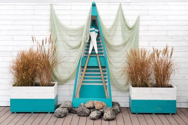 装飾的な漁網、木製のボート、パドルを備えた航海のコンセプト。写真撮影のためのマリンスタイルの屋外ロケーション。