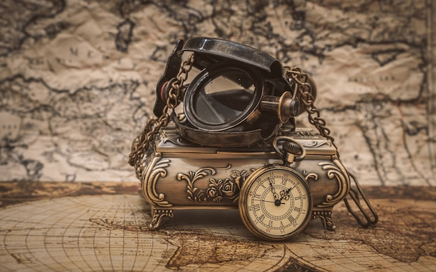 Nautical magnifying glass and watch necklace on map
